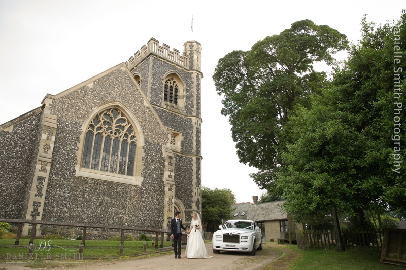 bride and groom with rolls royce outside church