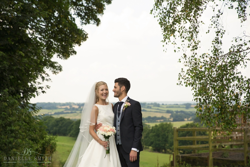 bride and groom with view of fields behind - havering-atte-bower
