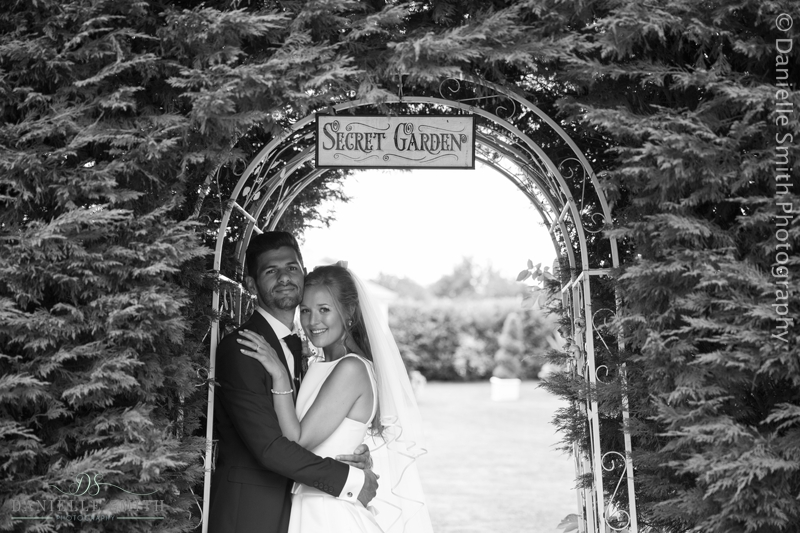 bride and groom under secret garden arch