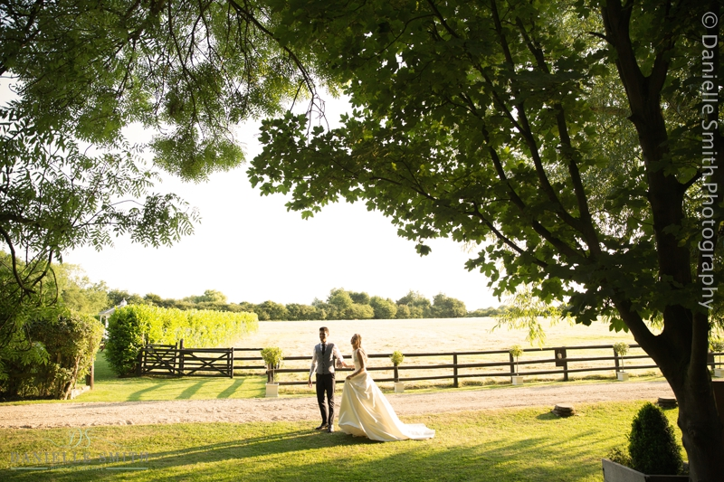 bride and groom walking on path in sunset - old brook barn wedding