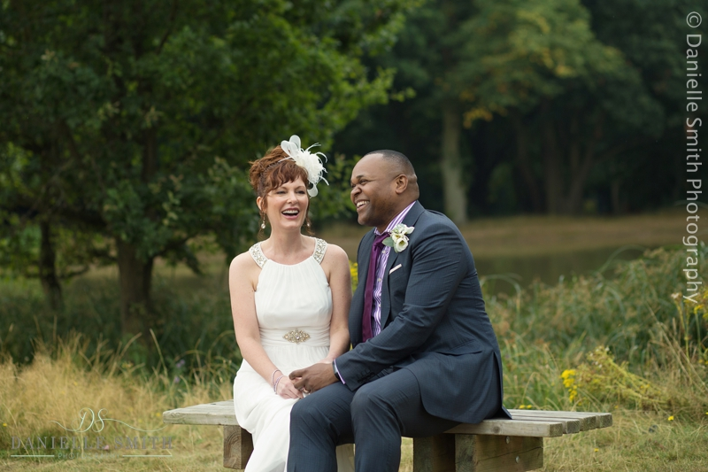 bride and groom sitting on bench in front of lake