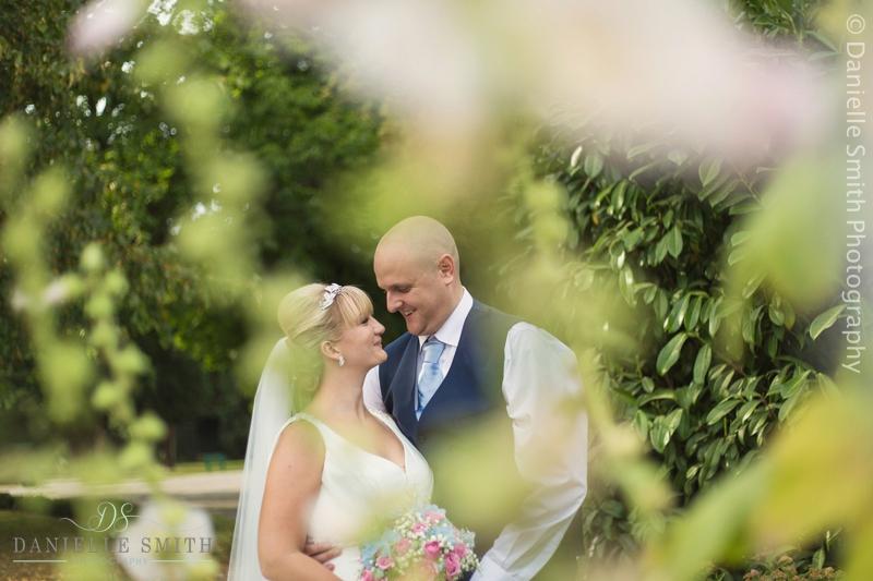 bride and groom through bush