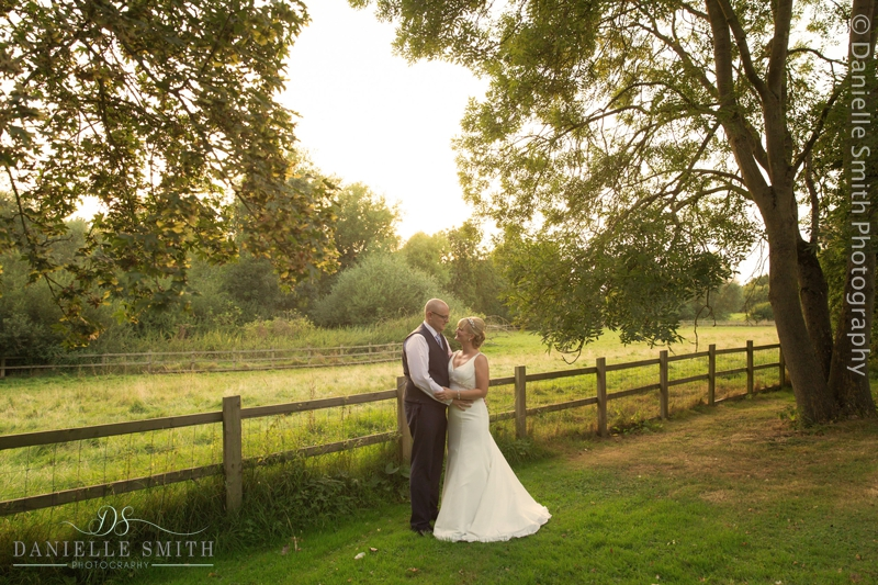 bride and groom in field at sunset