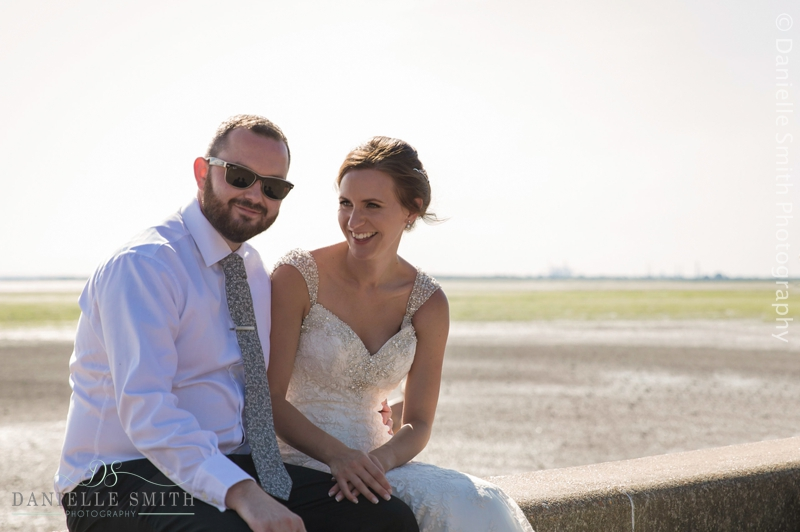 bride and groom laughing at beach