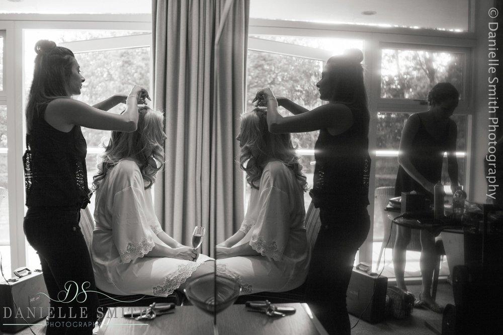 bride having hair done in mirror