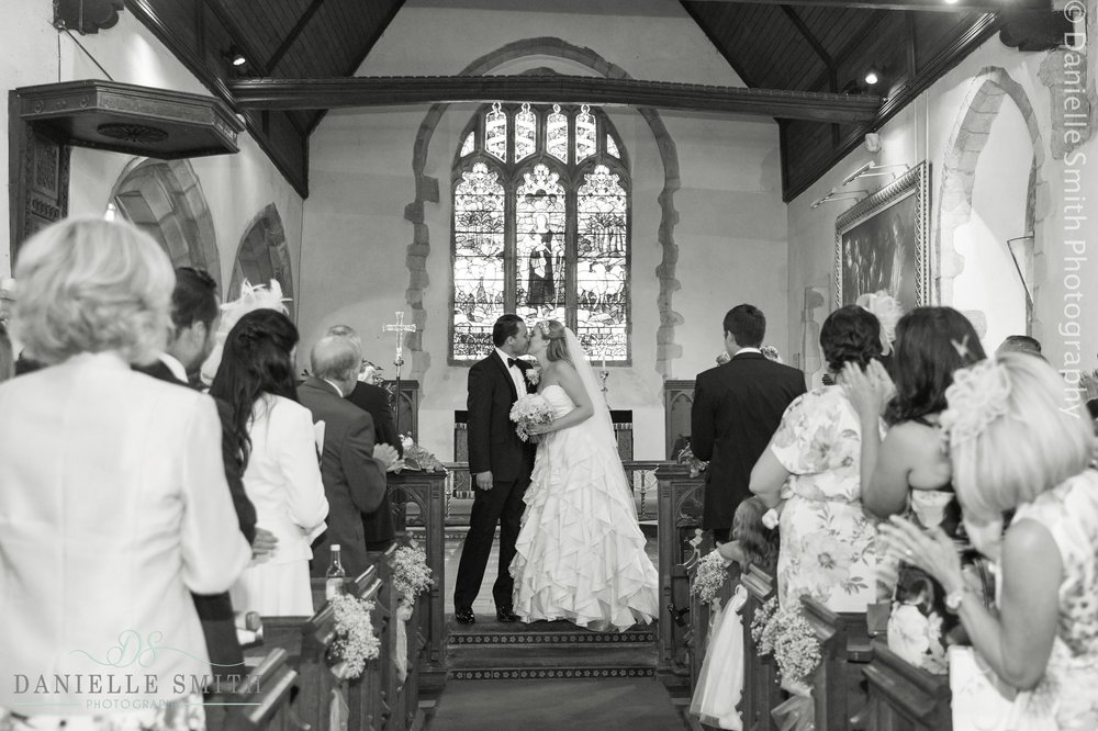 bride and groom first kiss at Hever church