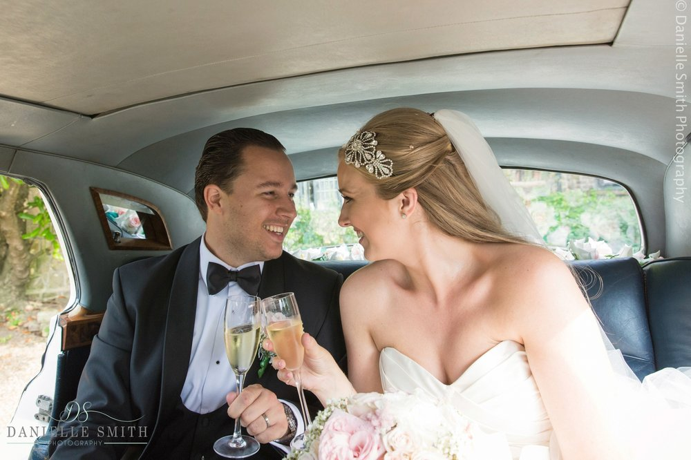 bride and groom toasting in wedding car - summer garden wedding