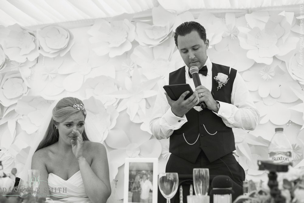 bride crying as groom gives speech