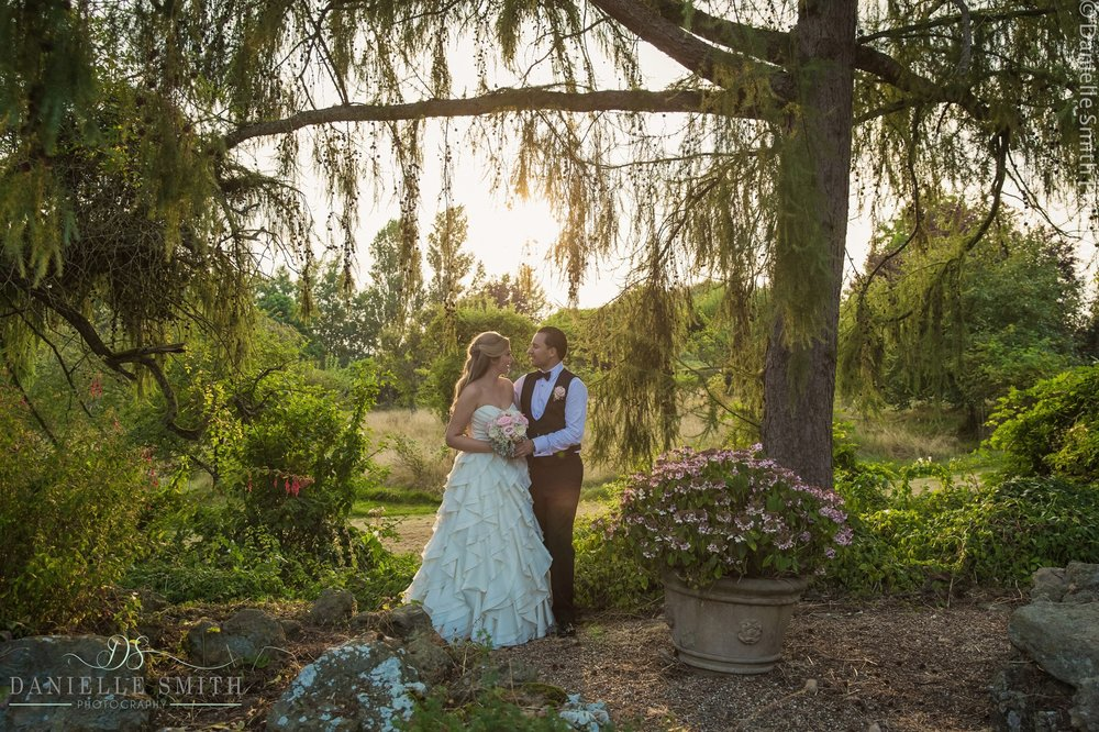 bride and groom in gardens as sun goes down