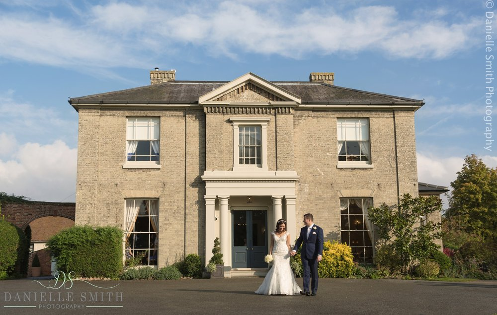 bride and groom walking in front of house at fennes
