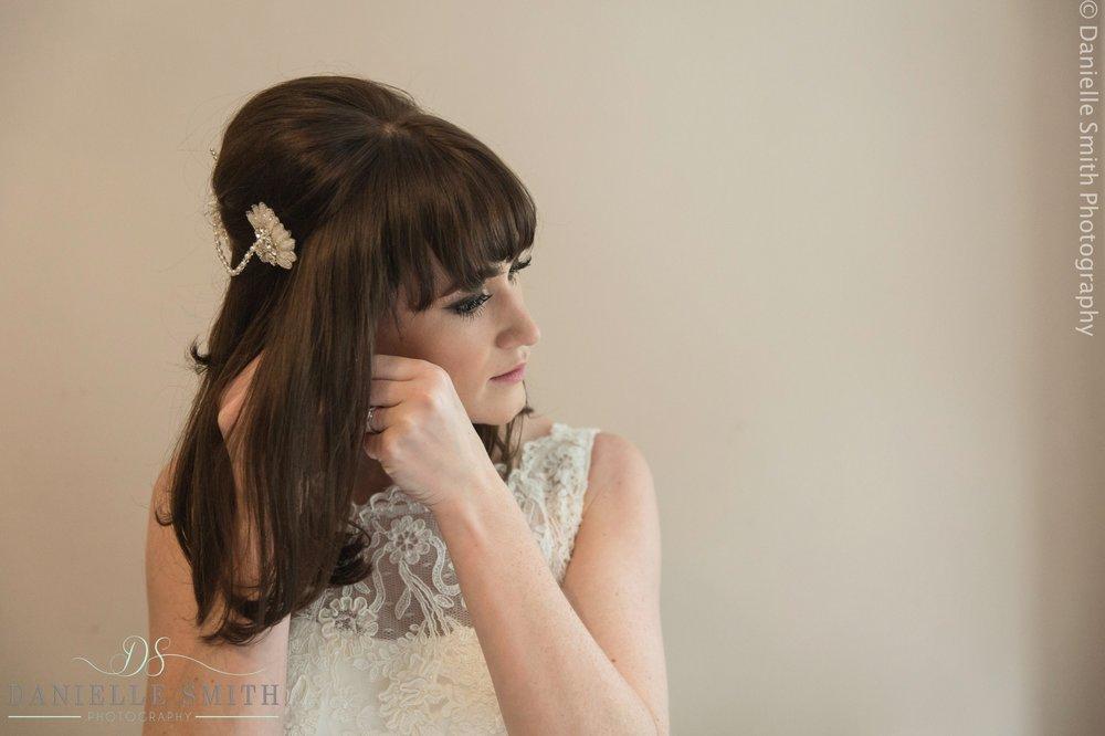 bride putting earrings in
