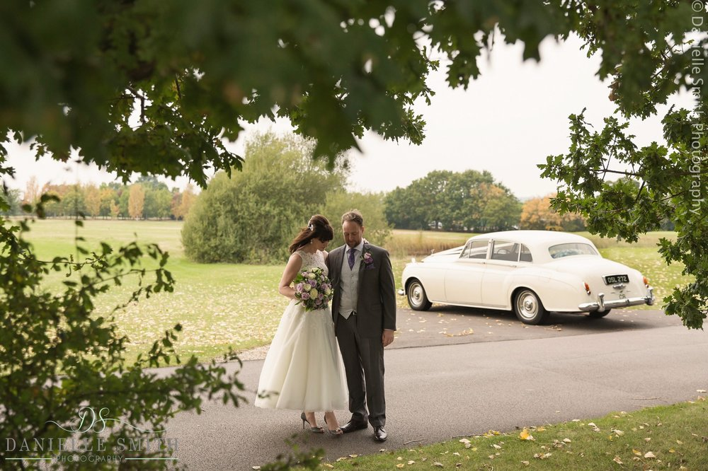 bride and groom with vintage car in background