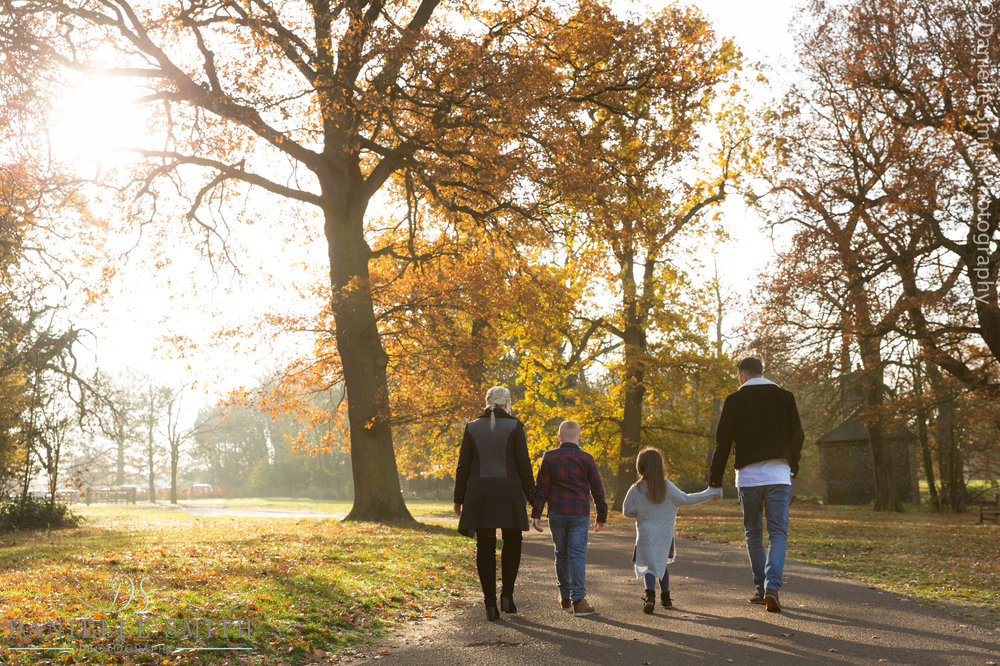 family of 4 walking in autumn park