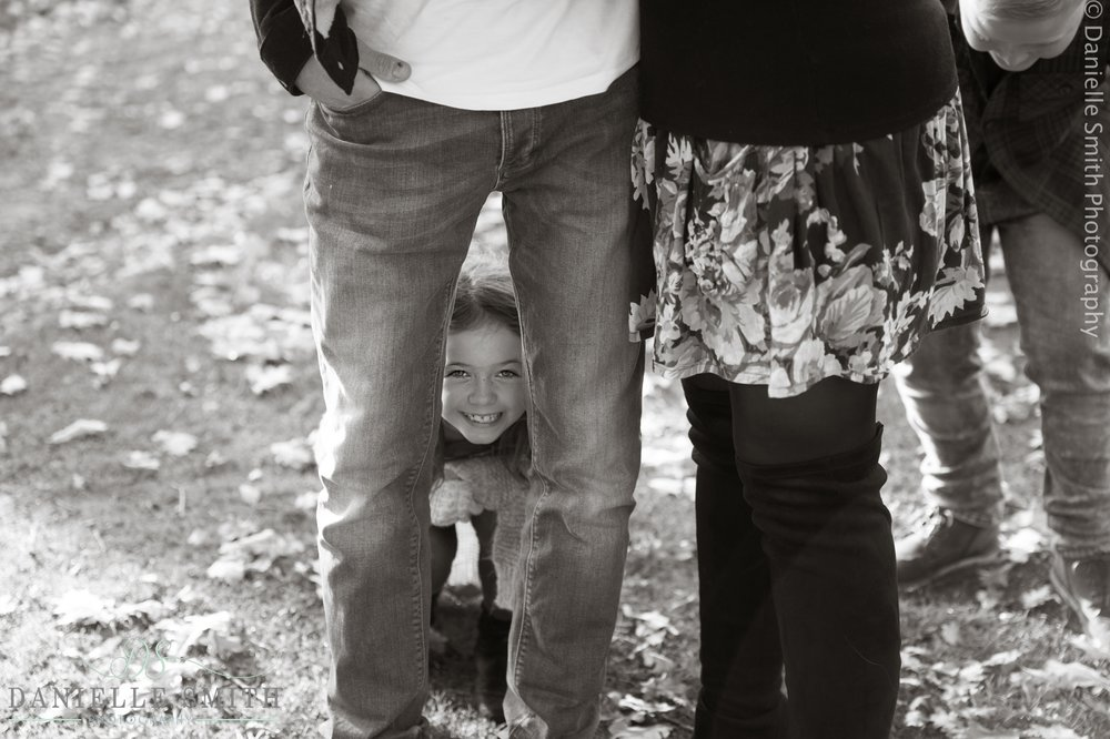 little girl between dads legs