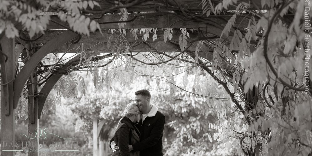 couple hugging under pergola in highlands park