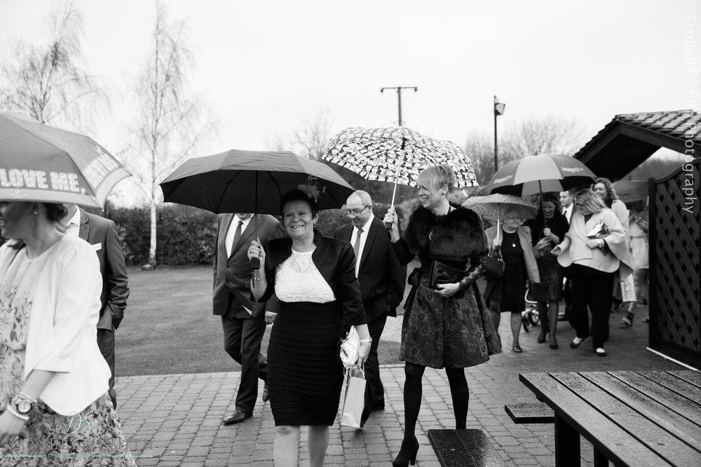 wedding guests arriving in rain with umbrellas