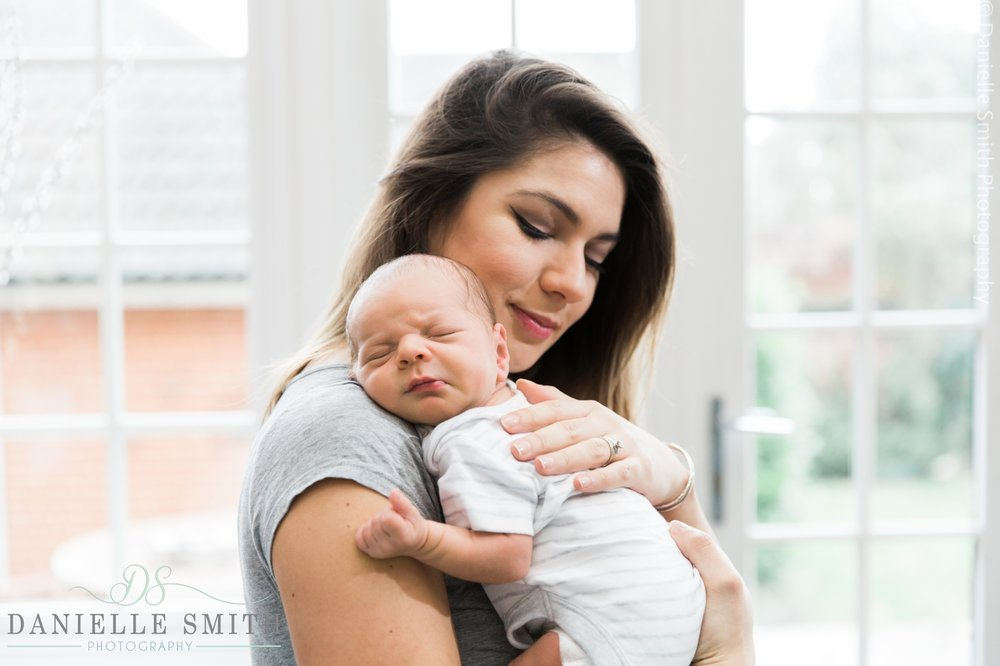 mum holding her baby boy on shoulder - newborn photography brentwood