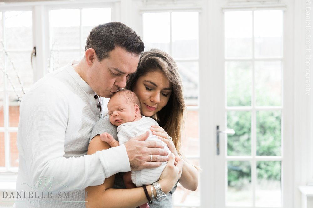 mum and dad holding new baby - newborn photography brentwood