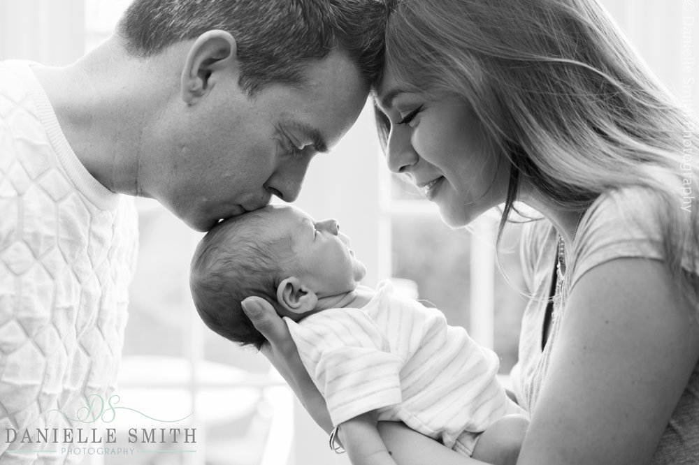 mum and dad kissing baby boy - newborn photography brentwood