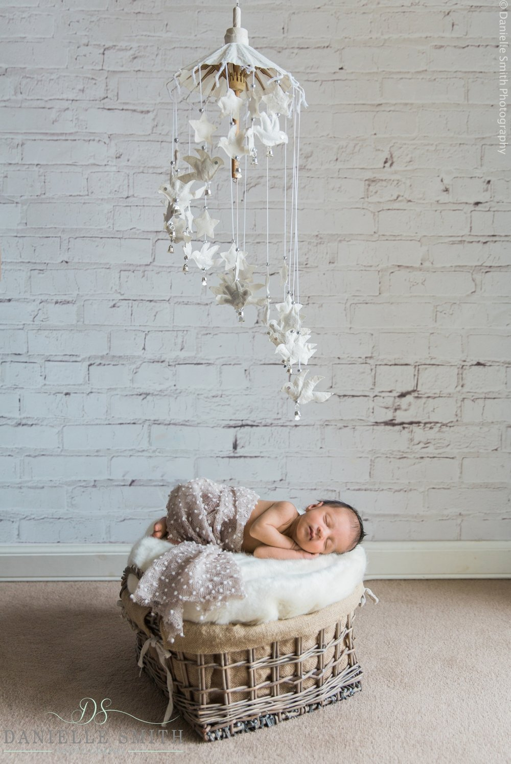 baby asleep in basket with mobile above