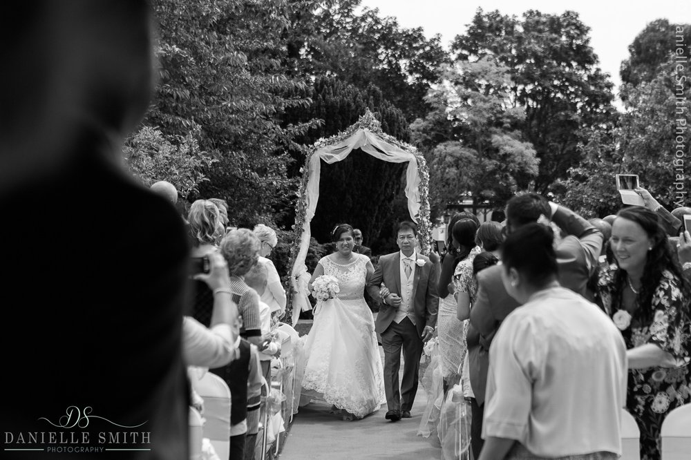 dad walking his daughter down the aisle at outdoor ceremony