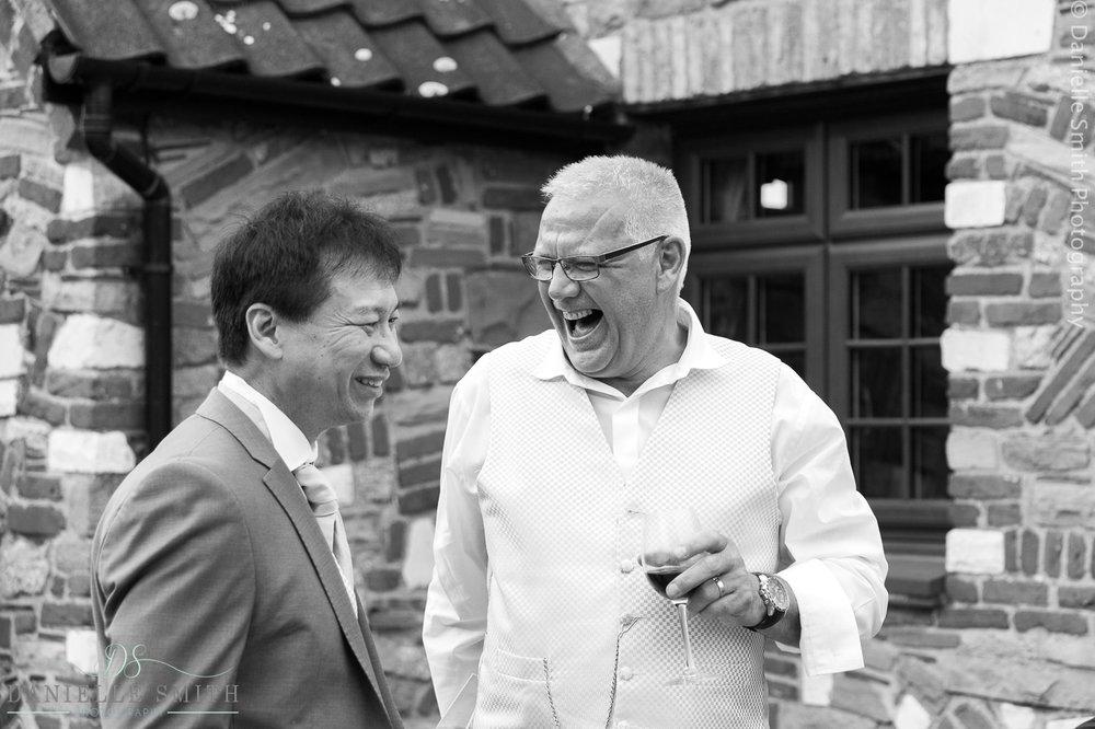 two men laughing at barn wedding