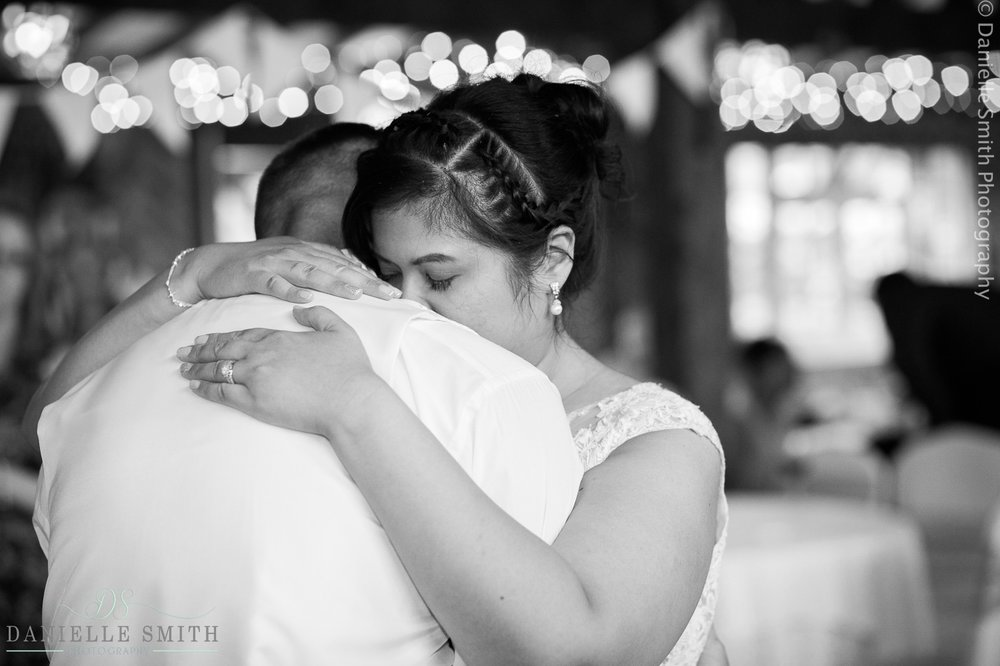 bride and groom hugging during first dance at barn wedding
