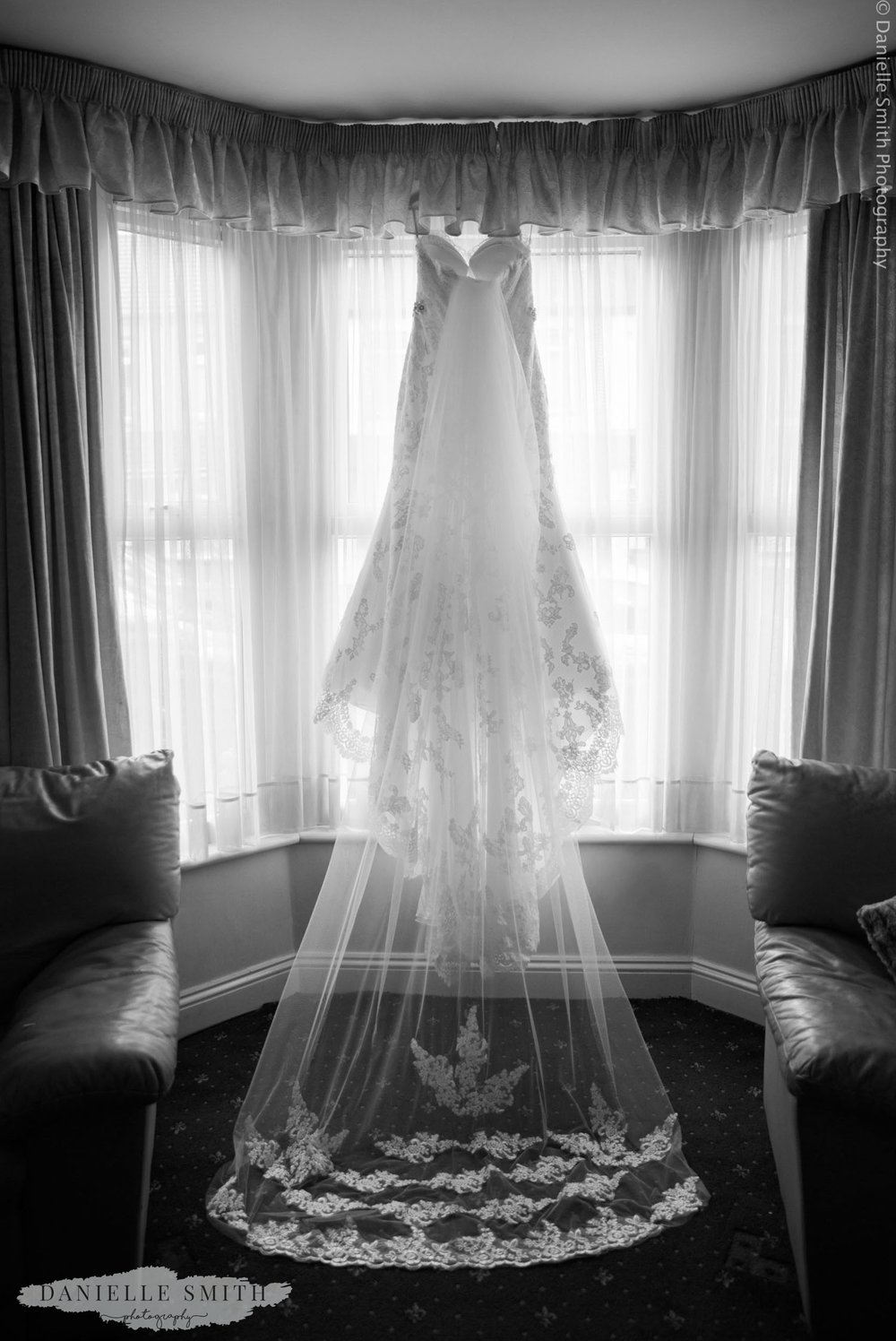 wedding dress and veil hanging in window