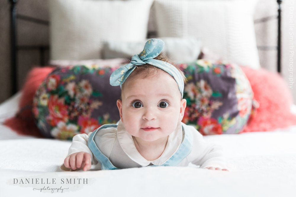 baby girl laying on front on bed - natural family photos