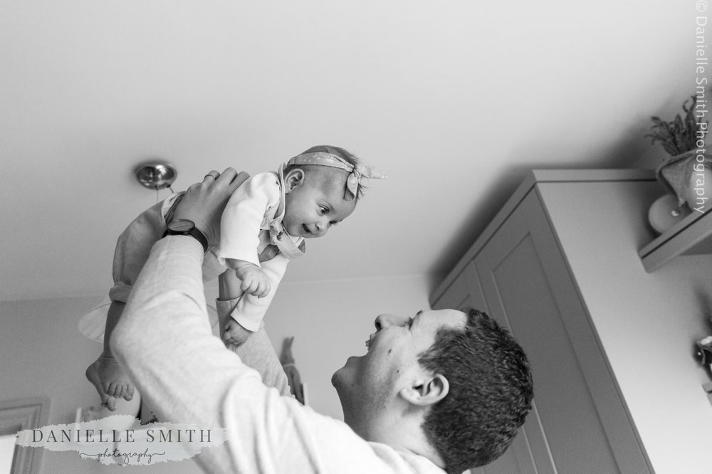 dad lifting baby up in air