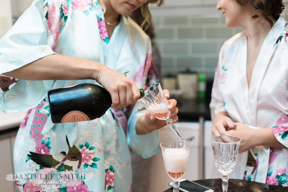bridesmaids pouring pink champagne