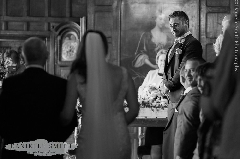 groom crying as bride walks towards him
