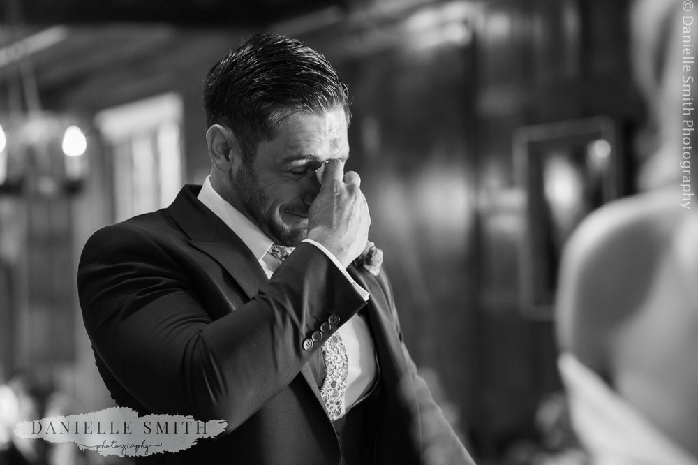 groom in tears while bride walks down the aisle