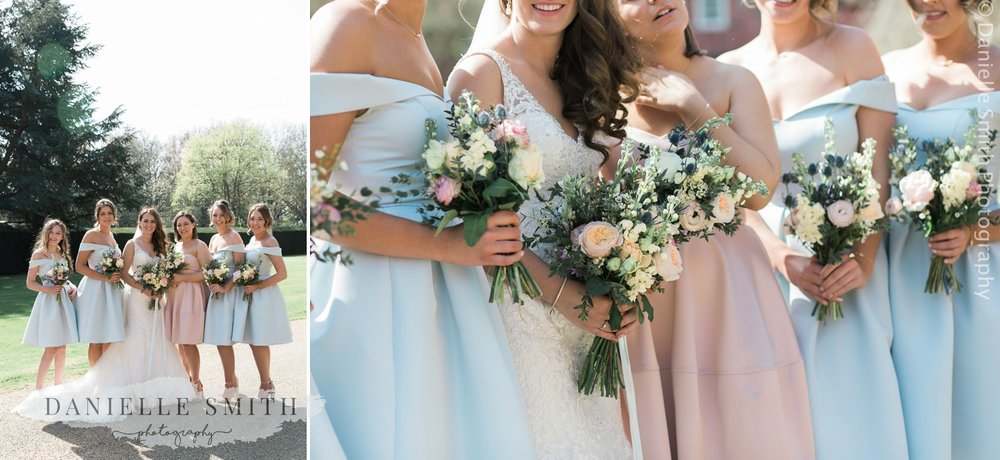 bride and her bridesmaids in pastel coloured tea length dresses and flowers