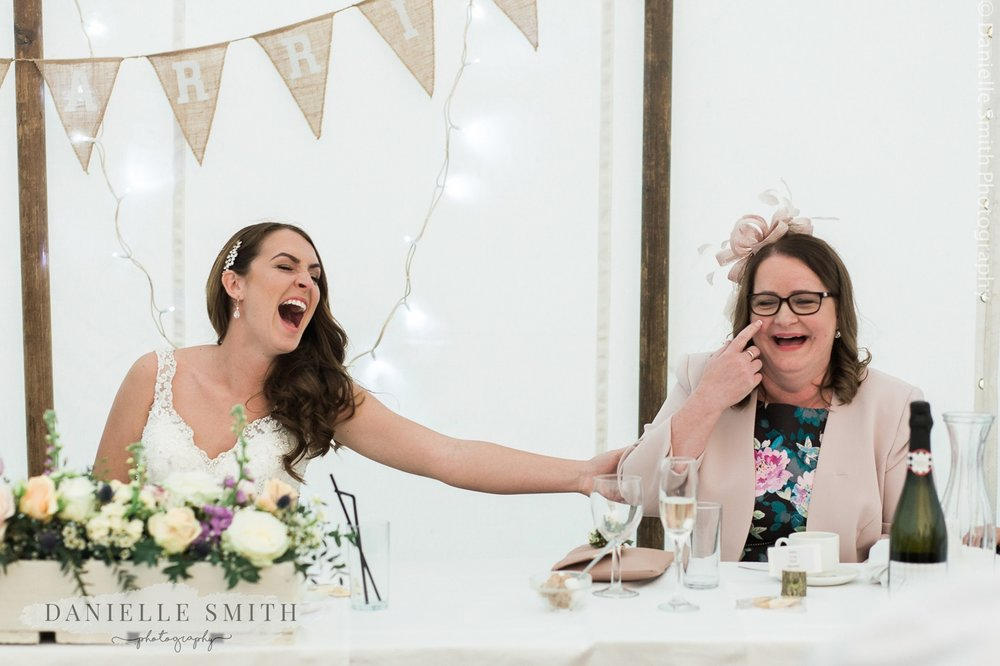 bride and her mum laughing during the wedding speeches