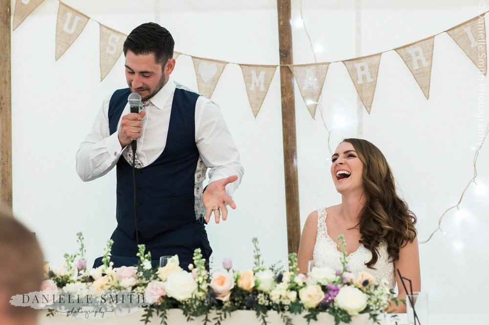groom giving speech and bride laughing
