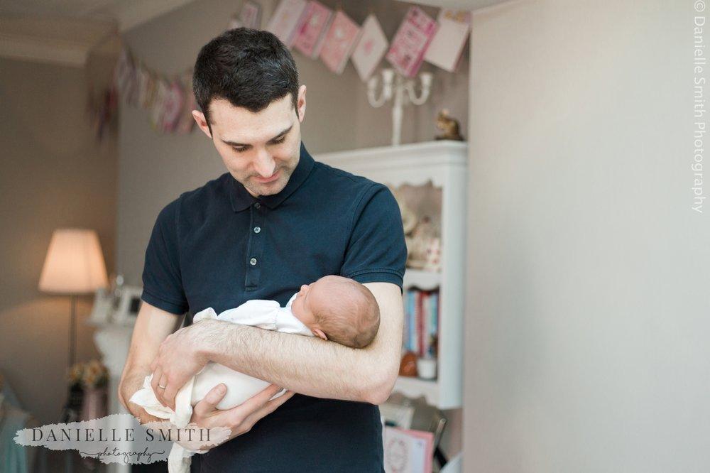 dad holding newborn baby - natural newborn photography