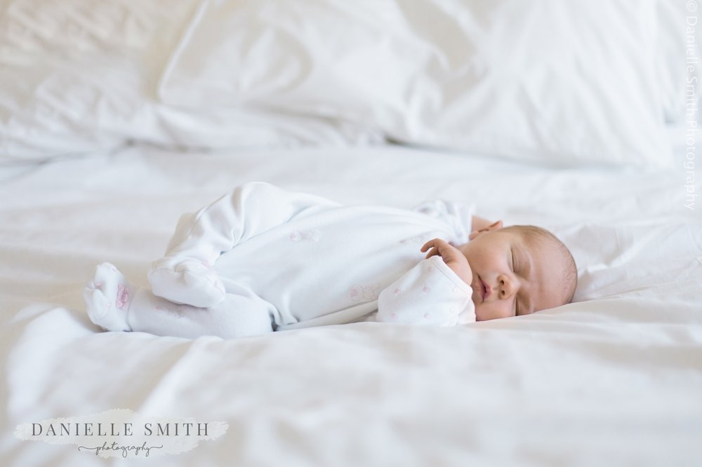 newborn baby laying on white bed at home