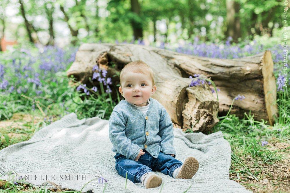 little boy sitting in woods