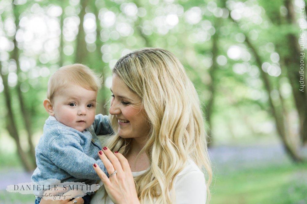 mum holding baby boy in woods