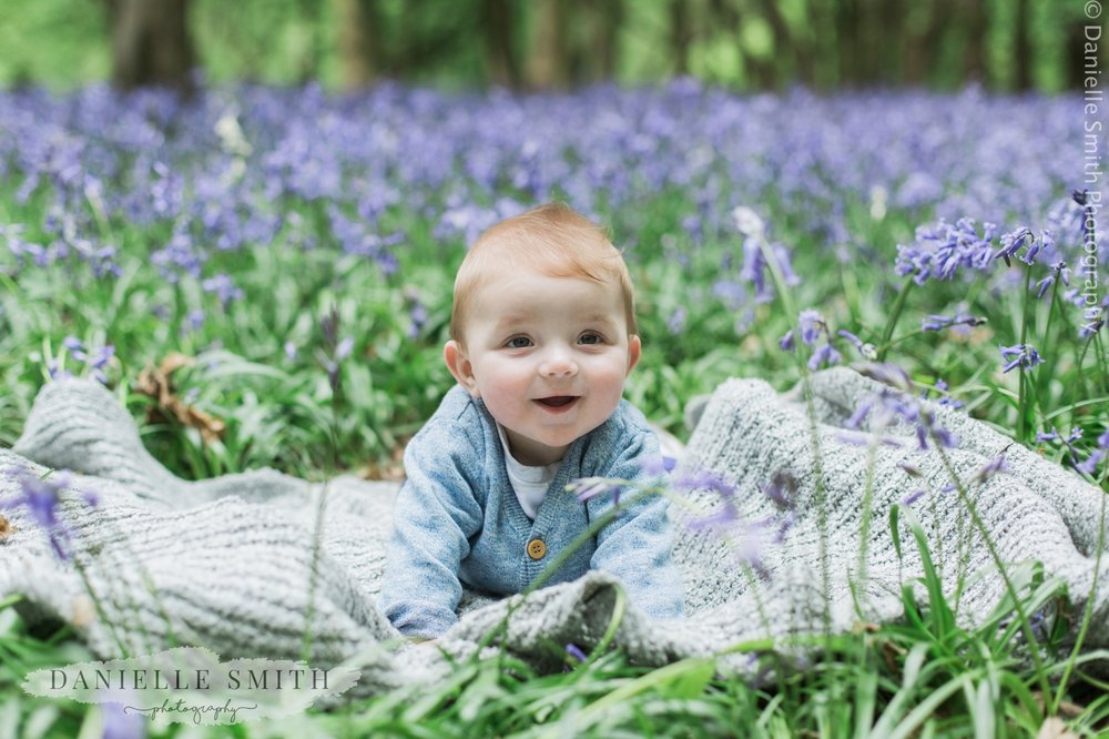 baby boy laying amongst bluebells - bluebell family photo shoot