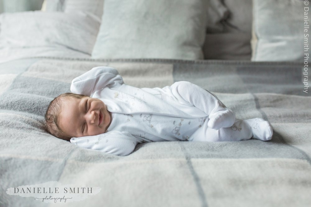 newborn baby laying on bed at home