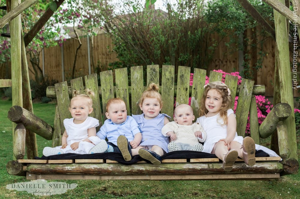 5 small children sitting on garden bench