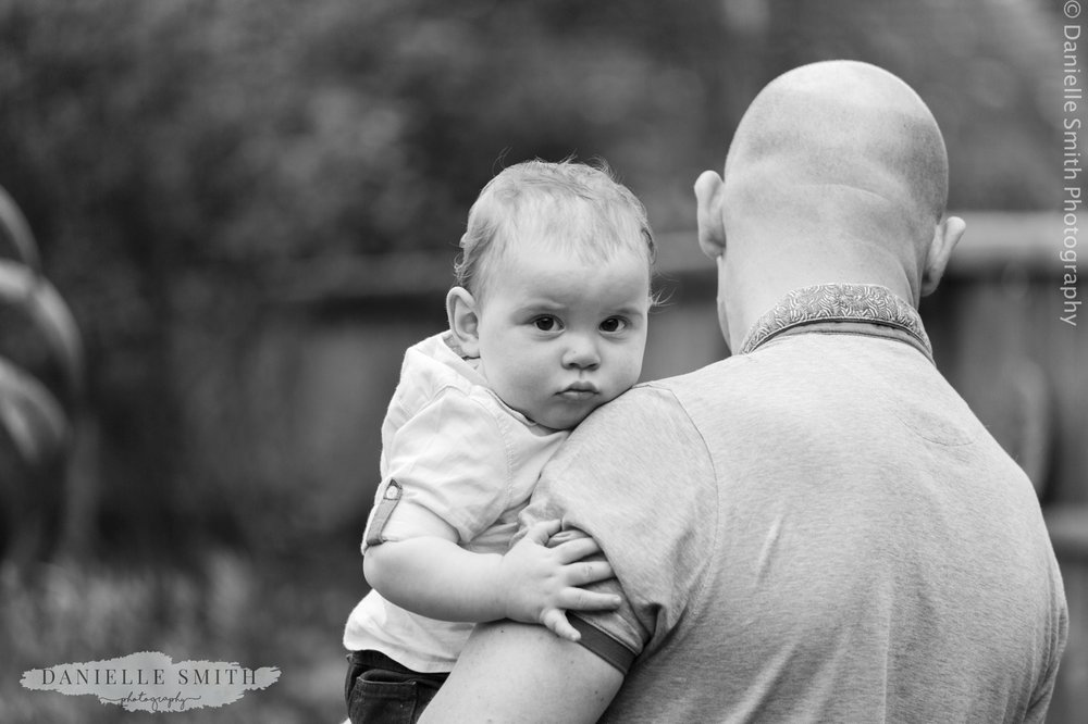 baby boy looking at camera in dads arms