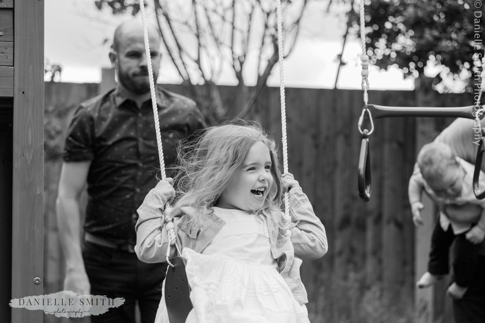 uncle pushing girl on swing