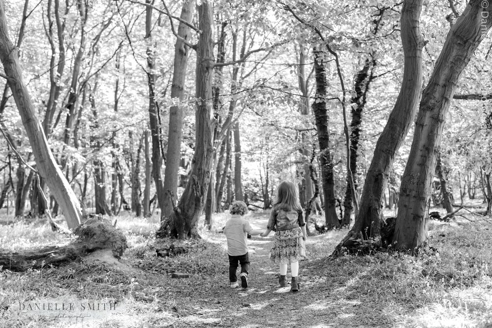 brother and sister holding hands in forest