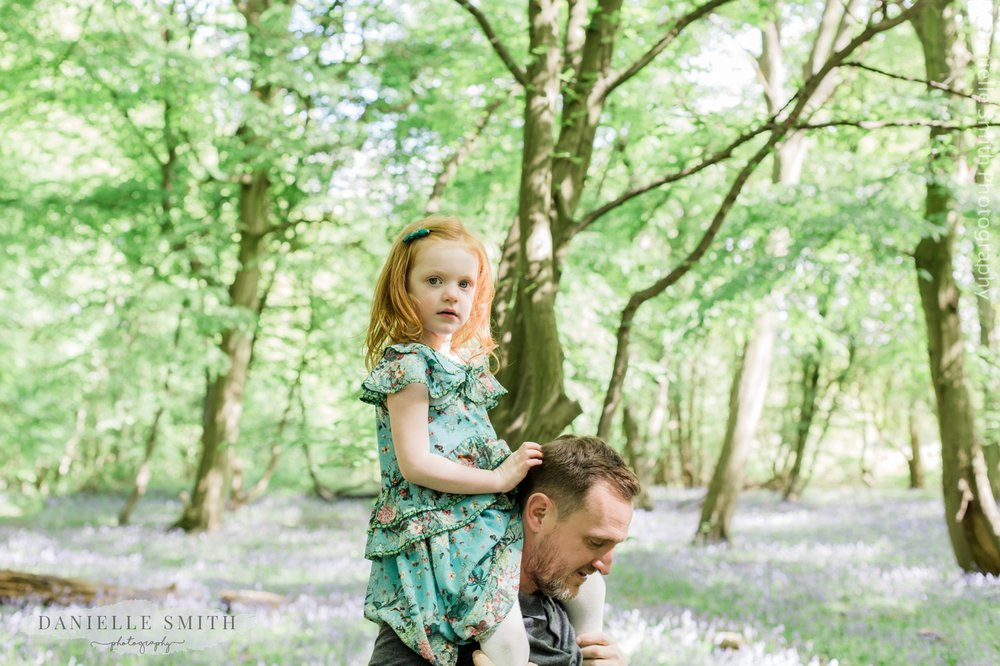 daughter on dads shoulder - family photos with bluebells