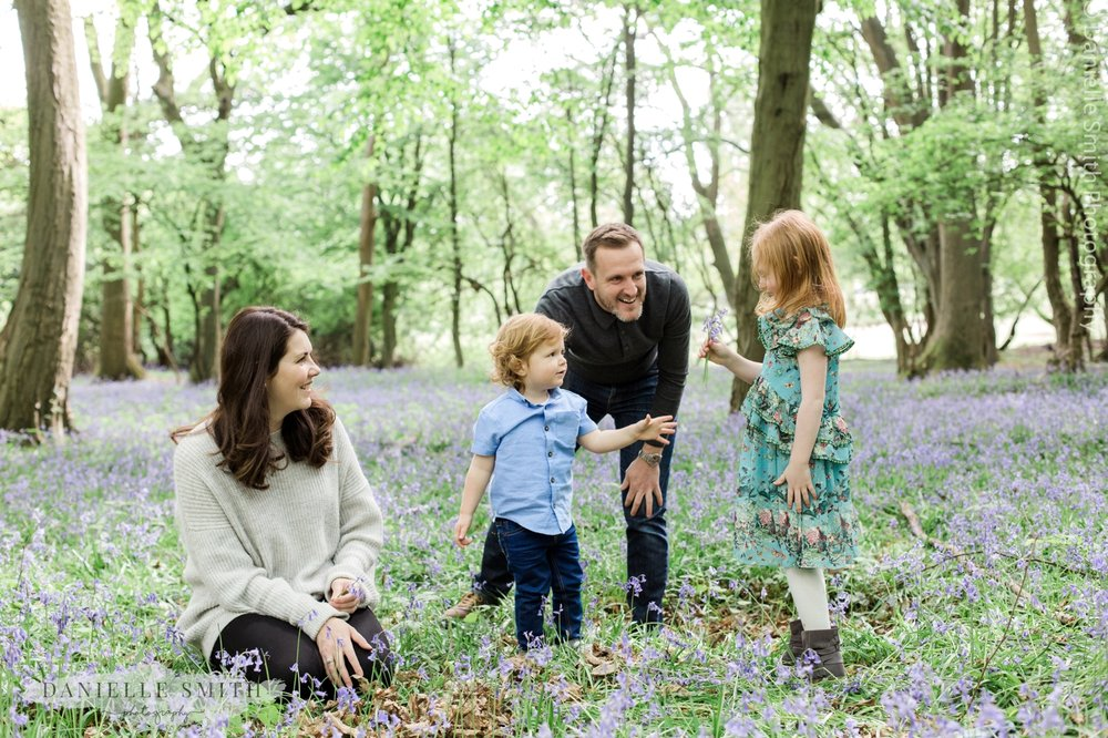 family having fun in bluebell forest