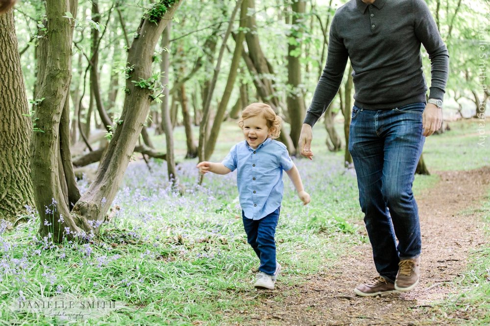 boy running with dad in bluebell woods
