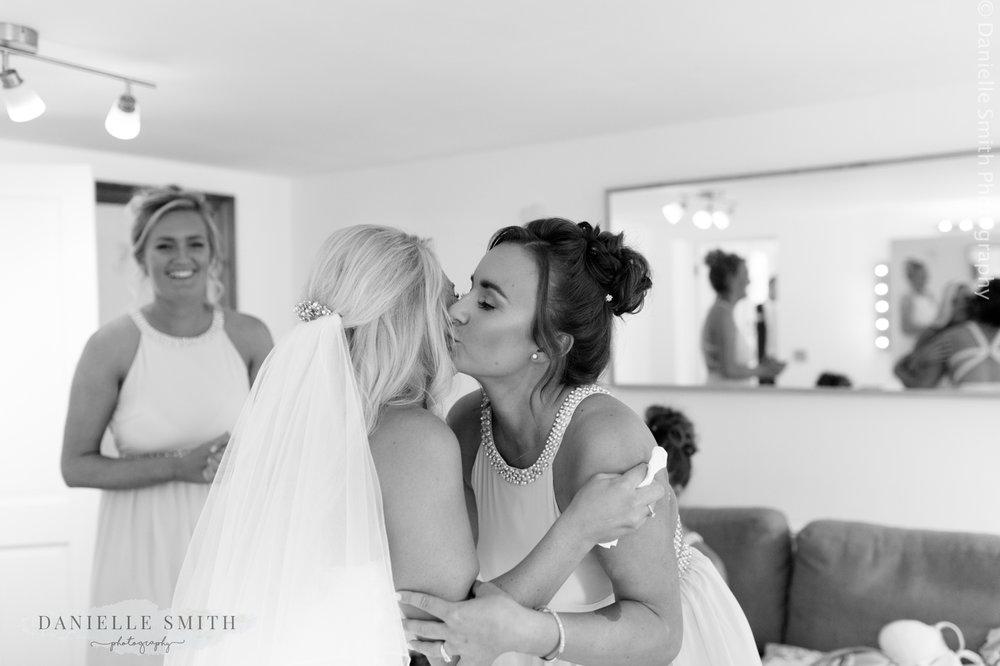 bridesmaid kissing bride